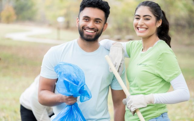 A young couple uses teamwork to work together on an outdoor community cleanup project together.  She rakes and he bags the leaves in a garbage bag.