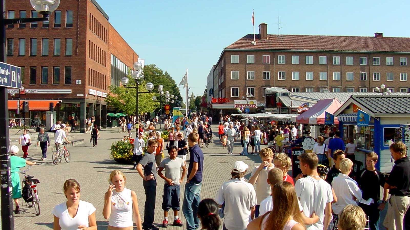 A photo of a street fair, showing people of diverse ages and bodies walking, biking, and talking in groups.
