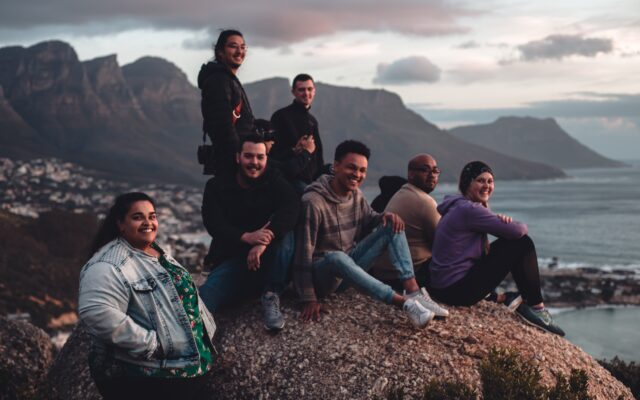 A group of diverse people sitting on a rock by the water and smiling.