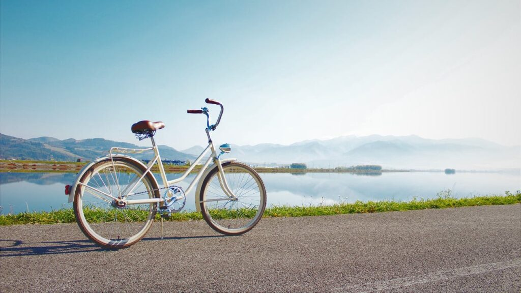 A bicycle on a street in front of a scenic body of water and mountains.