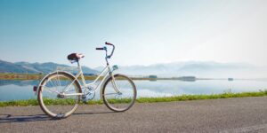 A bicycle on a street in front of a scenic body of wtaer.