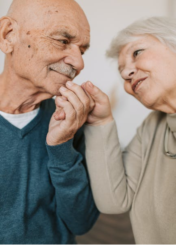 Elderly couple holding hands and looking at each other lovingly.