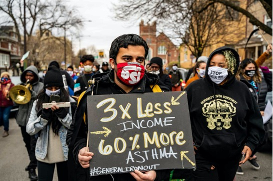 """Protester holding a sign that reads """"3x less income, 60% more asthma. #GeneralIronOut"""" to demonstrate how low-income areas are subjected to environmental hazards."""