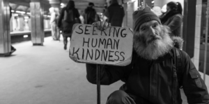 """Photographer met a man on the subway. The man has a sign that reads """"seeking human kindness""""."""