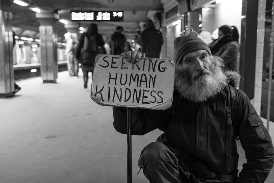 """Photographer met an older man on the subway. The man kneels in the subway station with a sign that reads """"seeking human kindness""""."""