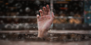 Person drowning in water and reaching a hand out.