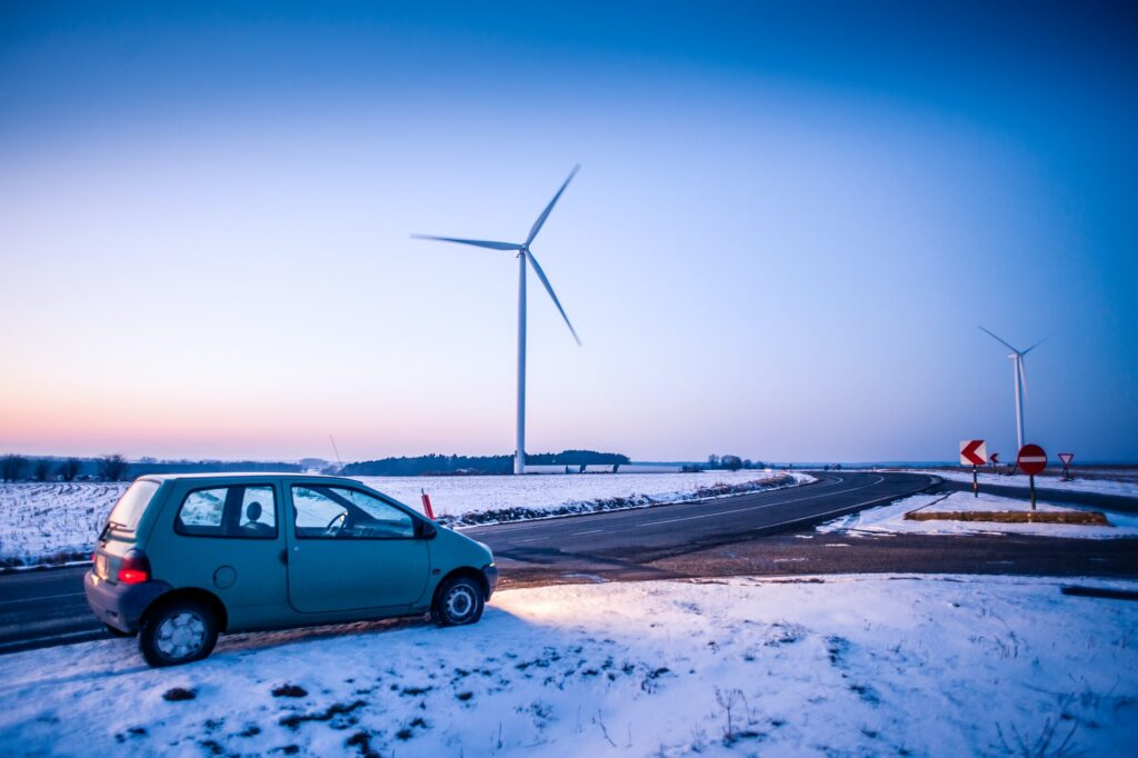 A car driving on a road on a snowy evening in front of a wind turbine.