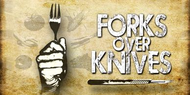 Forks Over Knives film poster, showing a hand gripping a fork.