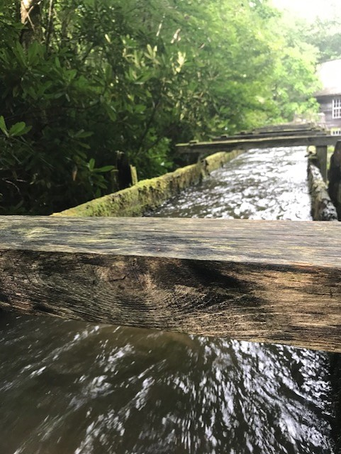 Photo of Mingus Mill in the Greta Smoky Mountains. A channel of running water runs underneath wooden beams.