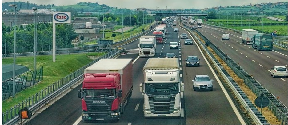 Many cars and trucks drive down a wide two-way highway.
