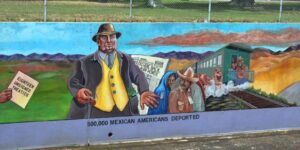"""A mural painted underneath a chain link fence of a line of Mexican Americans reluctantly boarding aa train while a man in a fancy suit and pockets full of cash pushes them onwards. A hand on the left hand of the mural holds a document labeled """"Eighteen Unsigned Treaties"""". Underneath the mural is written the words: """"500,000 Mexican Americans Deported."""""""