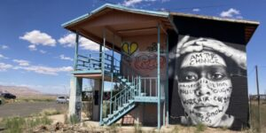"""A photograph of a Native American person placed on the wall of a small building as a mural. On the person's face is written the words: """"I am the change, industrialization, pollution, drought, water, air, earth, fake snow, co2."""
