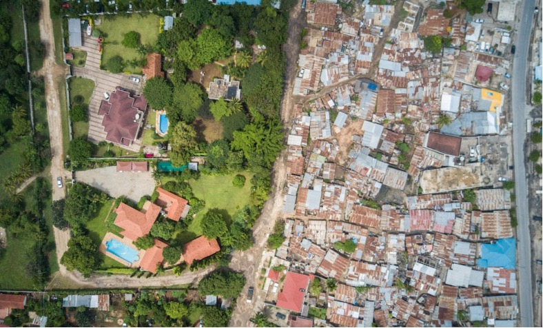Left side of the image shows a wealthy suburb with greenery with a neighboring slum on the right.
